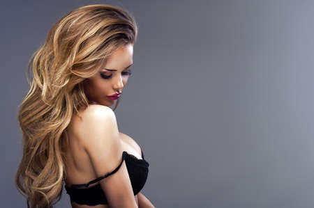 long curly hair: Beautiful sexy blonde woman standing, wearing black sensual lingerie, looking away. Stock Photo