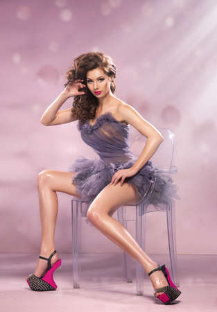 Fashion Dressed Sexy Girl Sitting on Chair. Woman in Purple Dress and High pink Heels photo