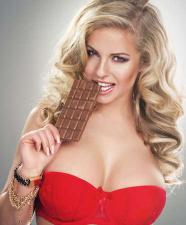 Portrait of a blonde young woman biting chocolate
