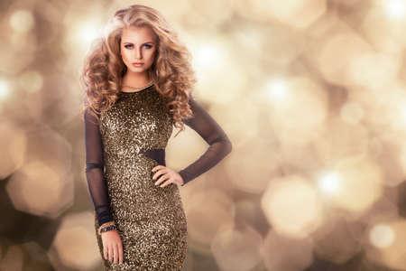 navidad elegante: Belleza de la mujer en traje de oro