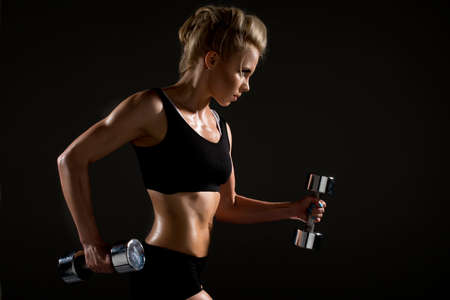 activewear: Sexy woman doing physical exercise with dumbbells Stock Photo