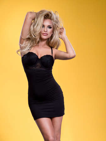 ragazze bionde: Sexy glamour giovane donna bionda in un sexy abito di lino in piedi contro uno studio sfondo giallo