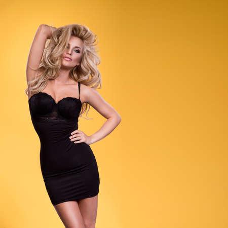 セクシーな魅力的な若いブロンドの女性黄色スタジオ背景に対してセクシーなリネン ドレス立って