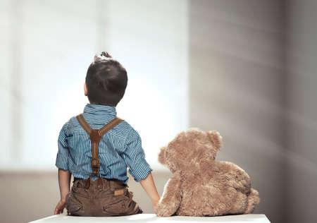 looking at view: Vista posteriore di piccolo ragazzo con l'orso