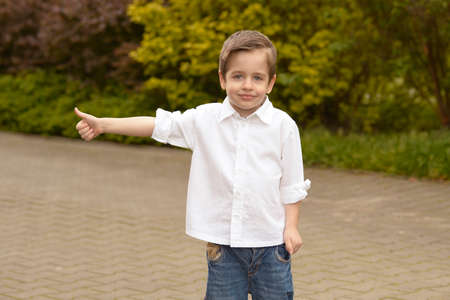 front or back yard: Portrait of cheerful boy showing thumbs up gesture
