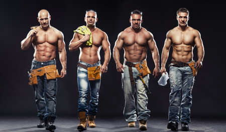 Groep van jonge knappe bouwer poseren, op een donkere achtergrond Stockfoto