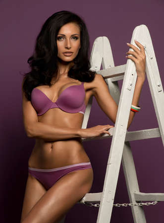 Glamorous busty brunette model with lovely long curly hair and a gorgeous figure posing in a violet bikini on a hot purple studio background with ladder photo