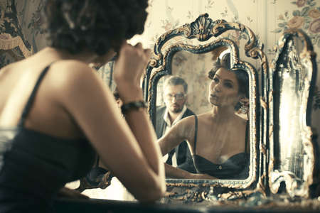 Lovely woman looking at mirror reflection. photo