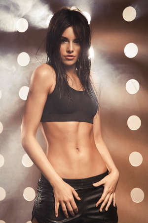 Young beautiful woman in fitness wear over modern background photo