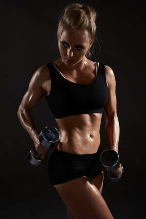 Sexy woman doing physical exercise with dumbbells photo