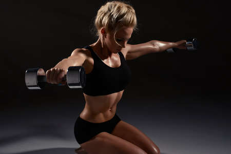 fitness abs female: Sexy woman doing physical exercise with dumbbells Stock Photo