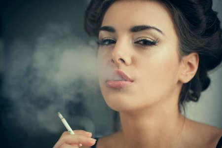 beautiful brunette woman smokes at home Stock Photo