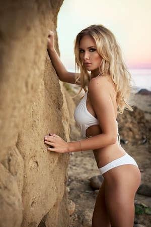 chica sexy: Muchacha atractiva joven en bikini de pie sobre las rocas de arena Foto de archivo
