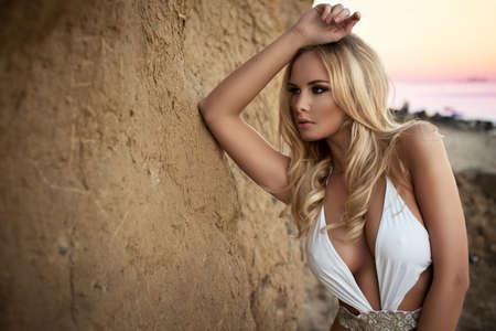 Sexy blonde Mädchen posiert auf einem Strand