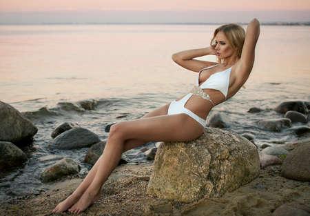 Sexy blond girl posing on a beach