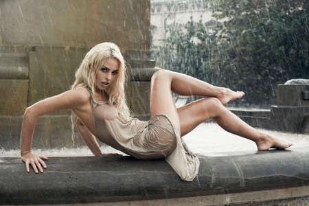 Mojado mujer joven atractiva en fuente de la ciudad en la lluvia