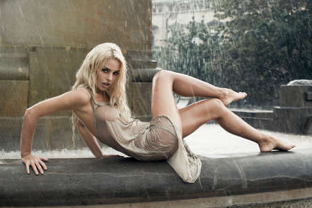 Sexy young wet woman in city fountain in rain photo
