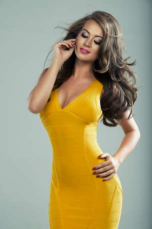 fashion photography: Happy blond woman in yellow dress in studio