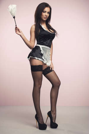 french maid: Beautiful woman posing in a skimpy maid uniform on a pink background