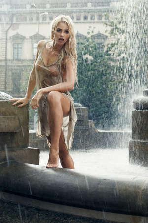 mojado: Mojado mujer joven atractiva en fuente de la ciudad en la lluvia