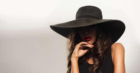 큰 가장자리와 빨간 입술을 입고 여름 검은 모자와 아름 다운 젊은 여자