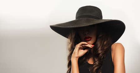 large: Beautiful young woman with red lips wearing summer black hat with large brim