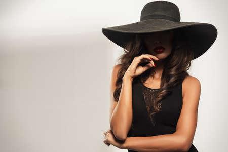 donne eleganti: Giovane e bella donna con le labbra rosse che indossa cappello nero estivo con tesa larga