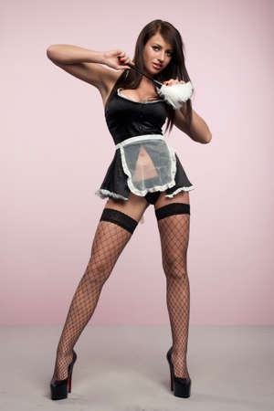 temptress: Beautiful woman posing in a skimpy maid uniform on a pink background