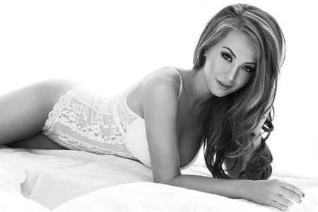elegant girl: Sensual beautiful blonde woman posing in elegant lingerie in bed. Girl looking at camera. Stock Photo
