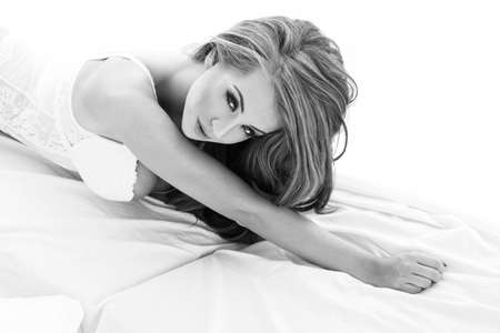 fetishes: Sensual beautiful blonde woman posing in elegant lingerie in bed. Girl looking at camera. Stock Photo