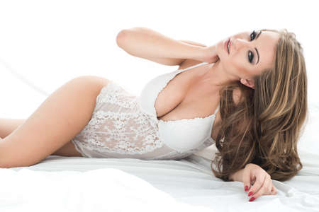 fetishes: Sensual beautiful blonde woman posing in elegant lingerie in bed. Stock Photo