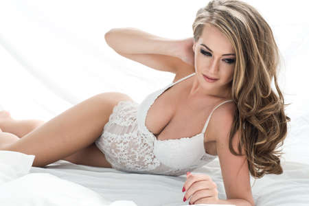 Sensual beautiful blonde woman posing in elegant lingerie in bed. Stock Photo