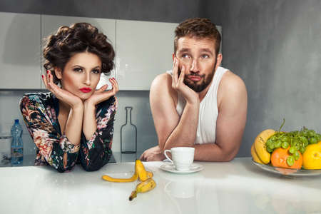 woman eating fruit: Funny couple after breakfast in kitchen