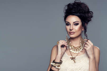 woman in cream lace blouse with jewelry Stock Photo