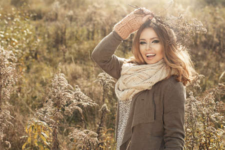 Young girl wear scraf and gloves. She smiling in autumn scenery Standard-Bild