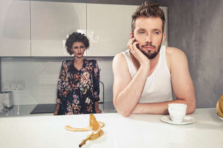 Funny couple after breakfast. Strange faces. Young man and beauty woman in kitchen photo