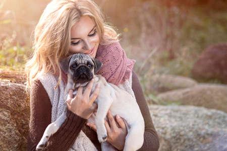 mujer con perro: Chica joven que sonríe en el paisaje de otoño con el perro pug