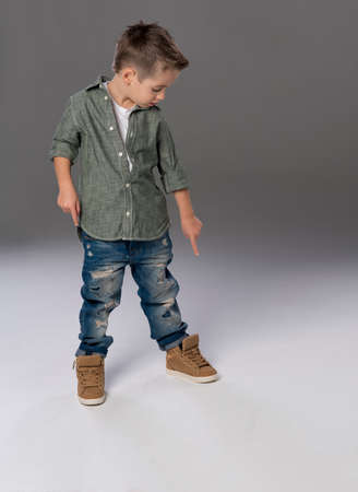 fashion boy: Fashion boy pointing down on grey background