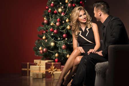 幸せな若い人々 はお互いにクリスマス ツリーの近くのギフトを与えます。