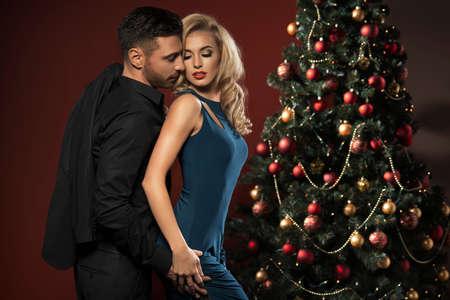 navidad elegante: Pareja feliz con el árbol de Navidad