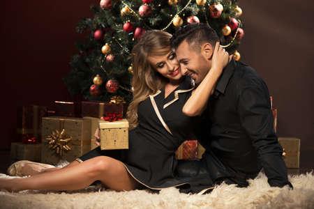 幸せな若い人たちはお互いクリスマスの木の近くのギフトを与えます。