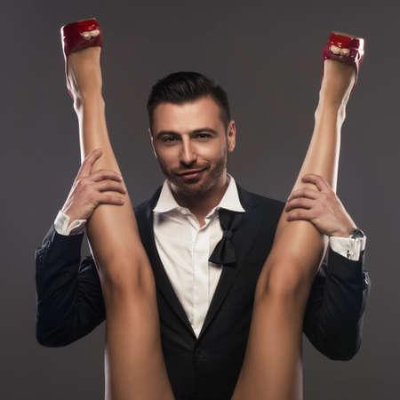 Elegenat man sitting and is spreading a woman's legs