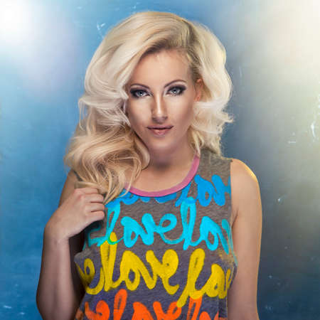 uñas largas: Belleza mujer rubia con el pelo rizado y colorido camiseta