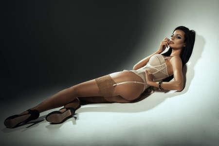 Сексуальная брюнетка женщина в белье, лежа на полу Фото со стока
