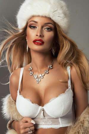 Sexy blonde woman with red lips wear fur