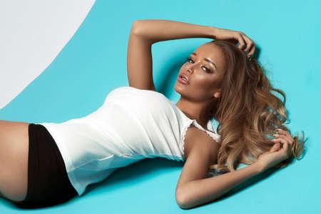 sexy young girl: Чувственный блондинка с длинными волосами, лежа на синем фоне в белой рубашке Фото со стока