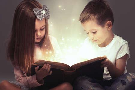 kinderen: Kleine paar opende een magische boek Stockfoto