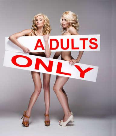 nude young: Две красивые молодые женщины, занимающие белая доска с текстом Фото со стока