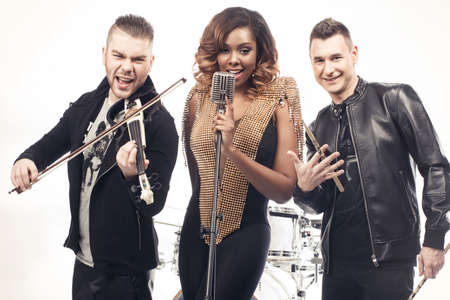 bassist: Fashionable music band posing. Two handsome man and beautiful sexy woman with music instruments