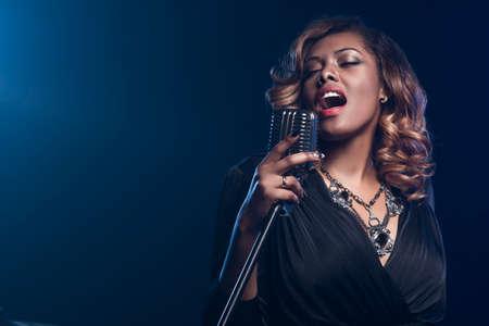 femmes souriantes: Belle femme africaine � chanter avec le microphone Banque d'images